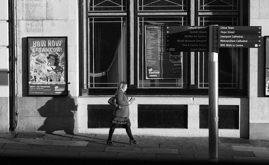 Shot of woman walking down street outside the Empire Theatre, Liverpool, black and white