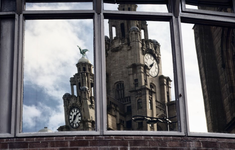 Two clock faces of the Liver Buildings reflected in the windows of the Atlantic Tower hotel