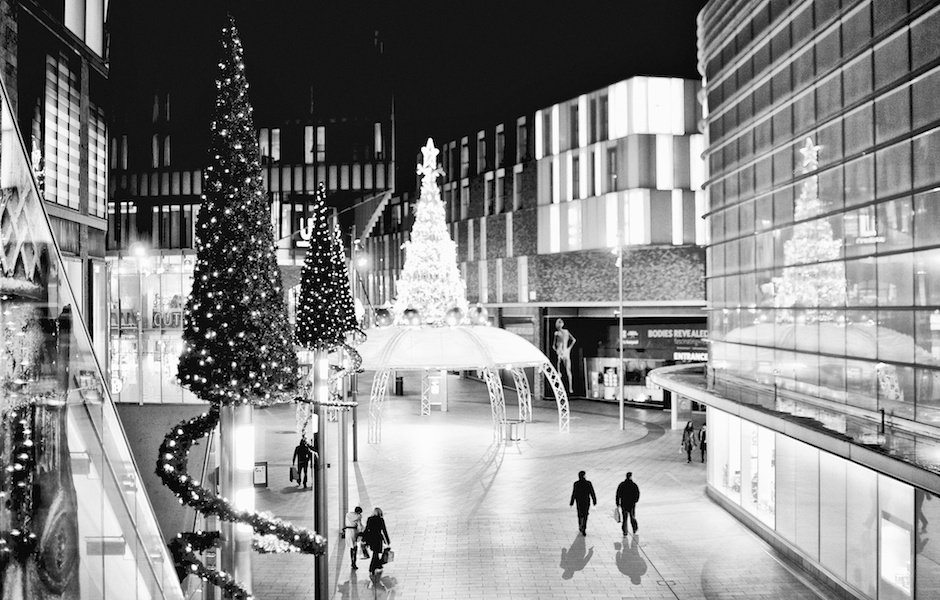 Black and white image of Christmas trees and Christmas shoppers in Liverpool One