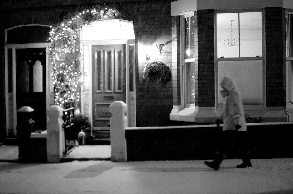 Woman walking past house with fairy lights, black and white, Allerton - Liverpool