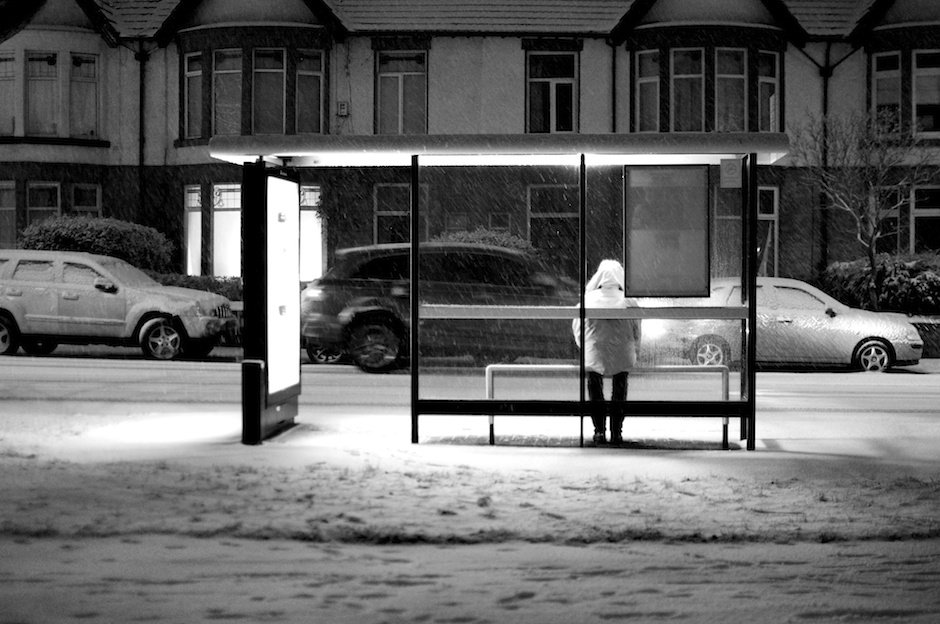 Woman waiting at bus stop in snow, black and white, Green Lane - Liverpool