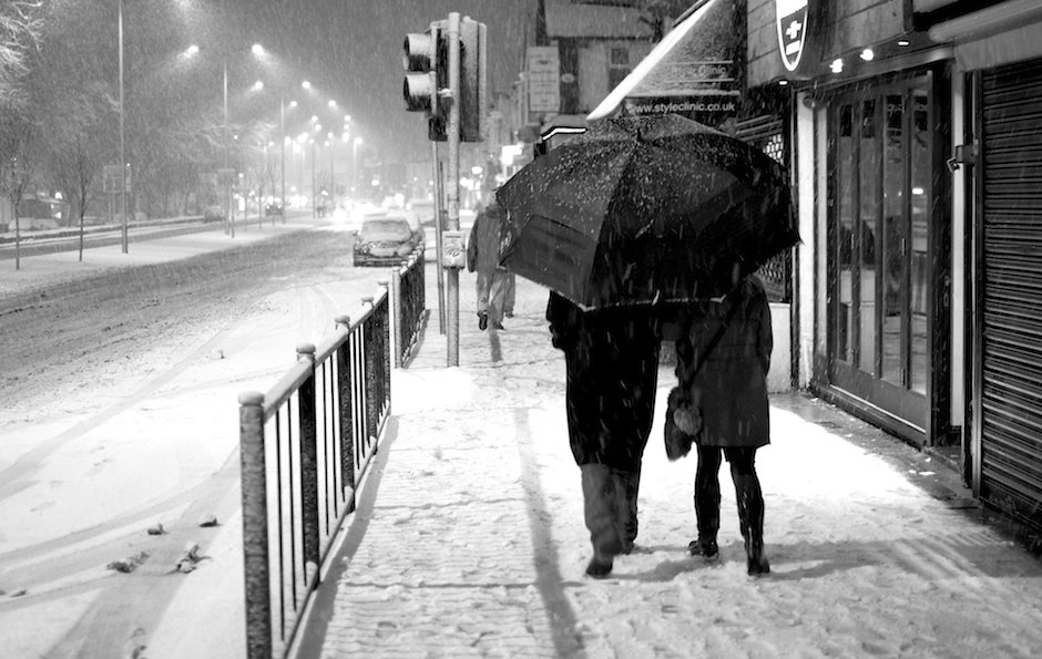 Black and white image of couple with large umbrella walking in snow - Allerton Road, Liverpool