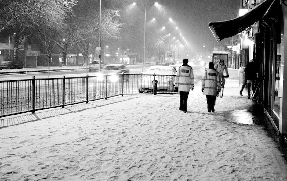 Police community support officers walking down Allerton Road in snow, Liverpool