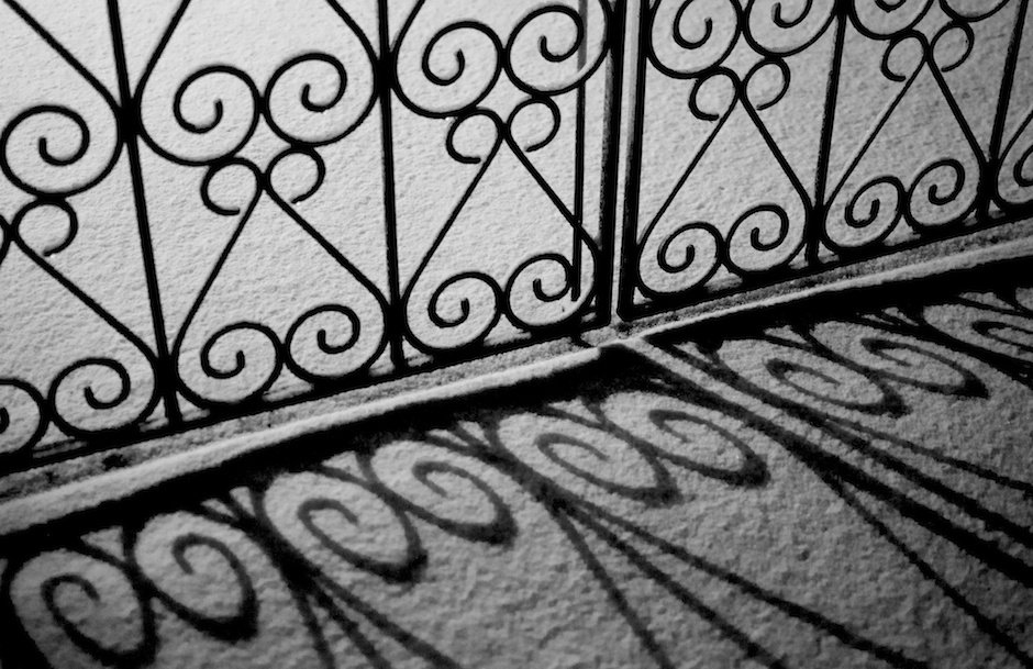Black and white detail of gate and shadow in snow