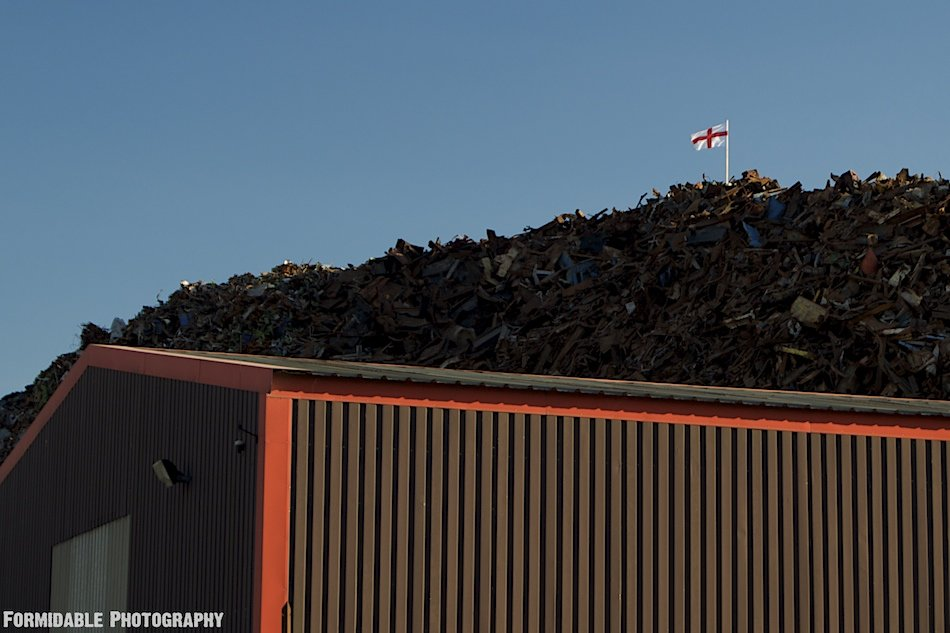 England St.George Cross football World Cup flag flying on top of massive scrapheap, Widnes, UK