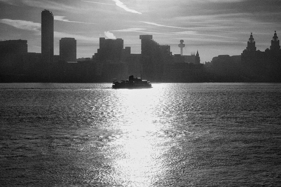 Ferry crossing the Mersey in front of Liverpool waterfront, black and white.
