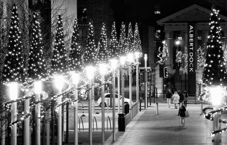 Black and white view towards Albert Dock showing Christmas decorations and Christmas shoppers, Liverpool
