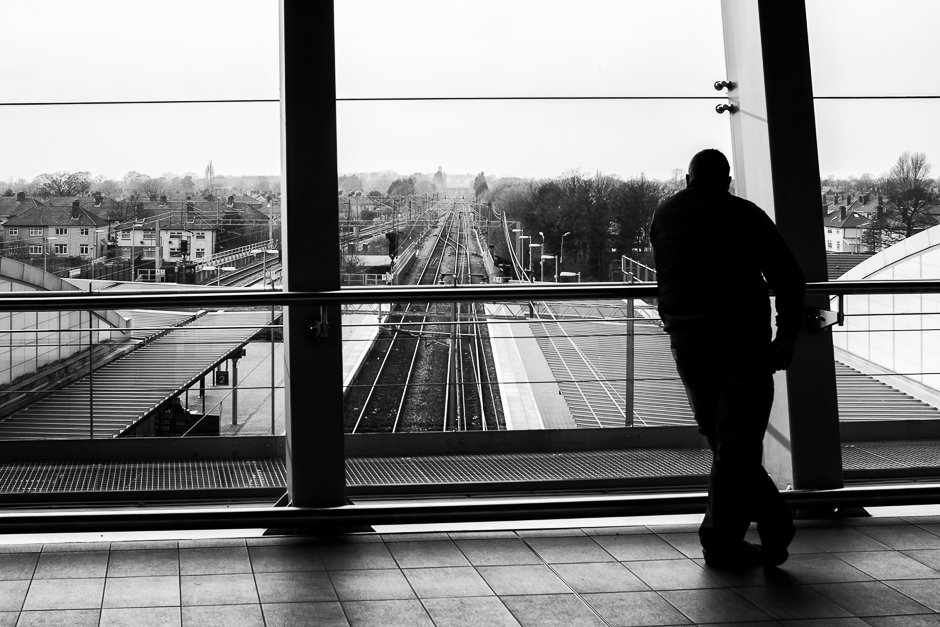 Black and white image of man looking out of window, Liverpool South Parkway