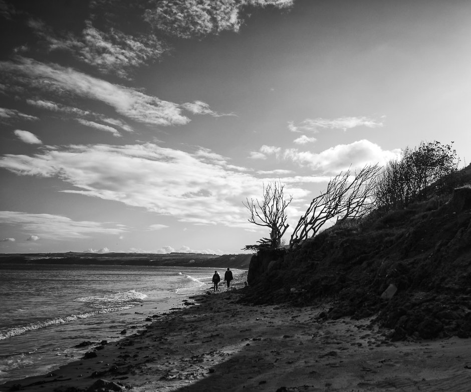 Couple walking along coast, Filey
