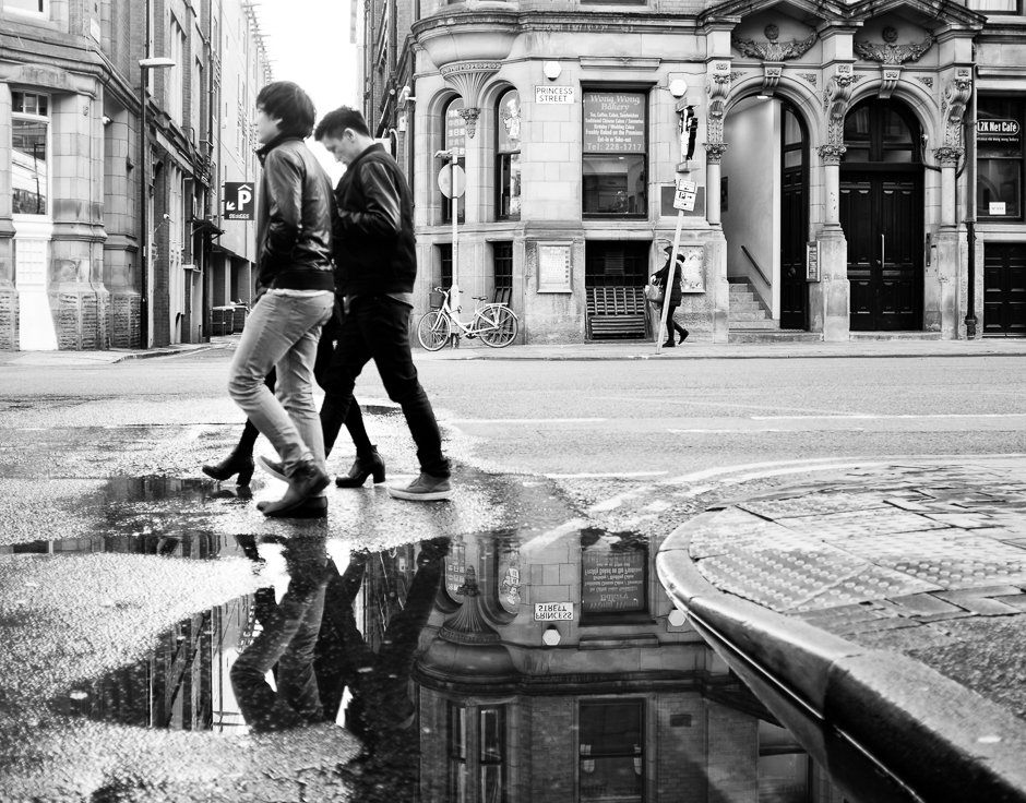 Reflection in a puddle of group of men crossing road, Manchester