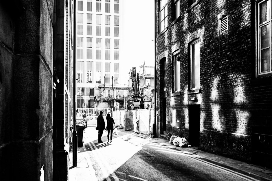 Black and white image of couple looking at building being demolished, Manchester