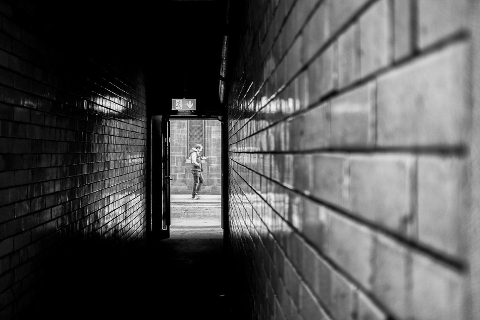 Image of man at end of tiled pub alleyway, Manchester